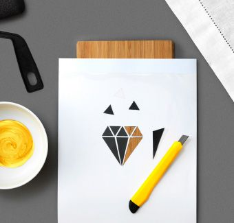 A Diamond Shape Being Cut Out Of A Piece Of Paper Using A Utility Knife And