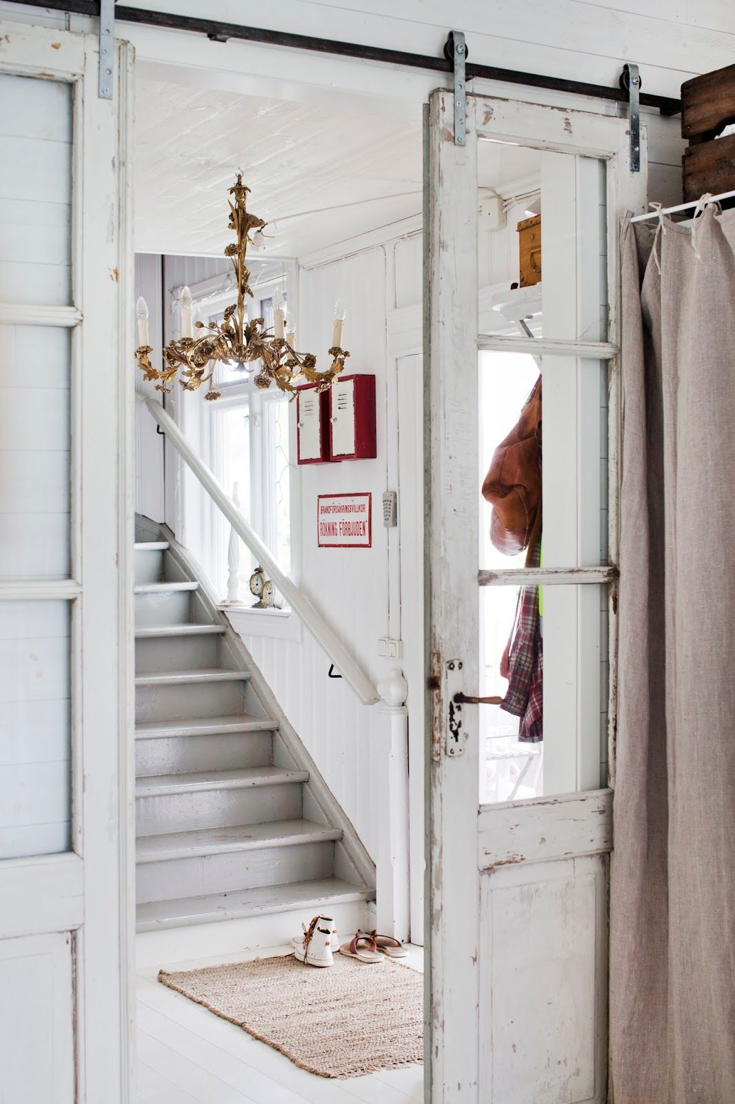Vintage Windowed Doors On Sliding Tracks Give This Space An Airy