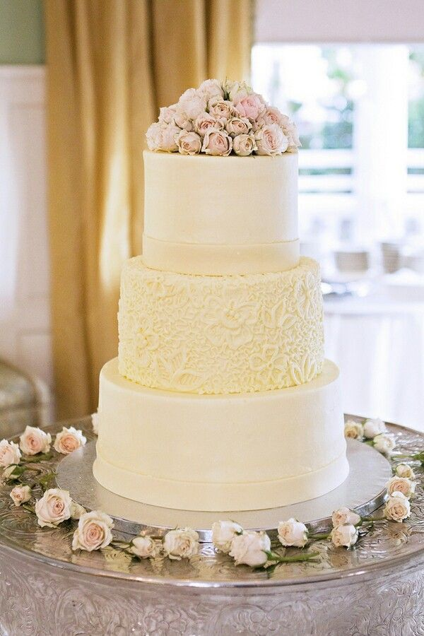 White and cream cake with lace effect on 2nd to bottom tire ...