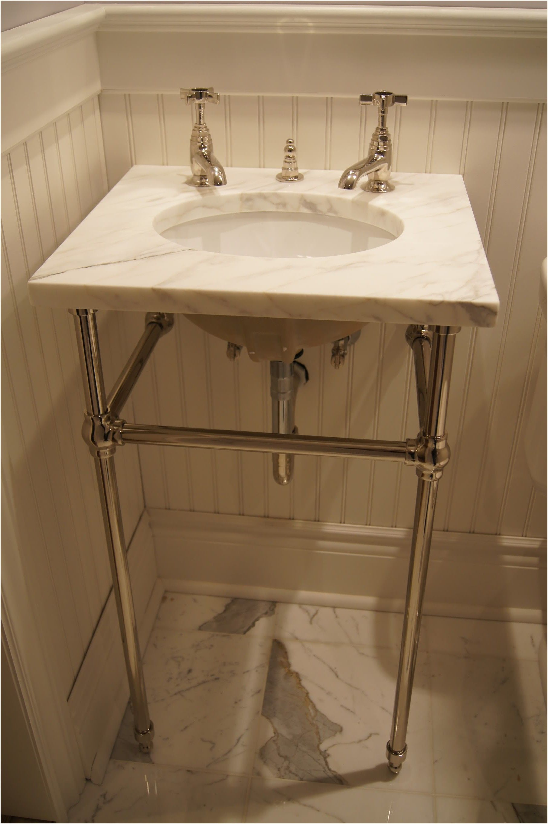 undermount sink with a marble top on console legs remodeled from