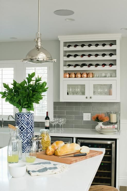 Fabulous kitchen features a glass front wine fridge tucked under a white quartz countertop as well as a glossy gray linear tiled backsplash.