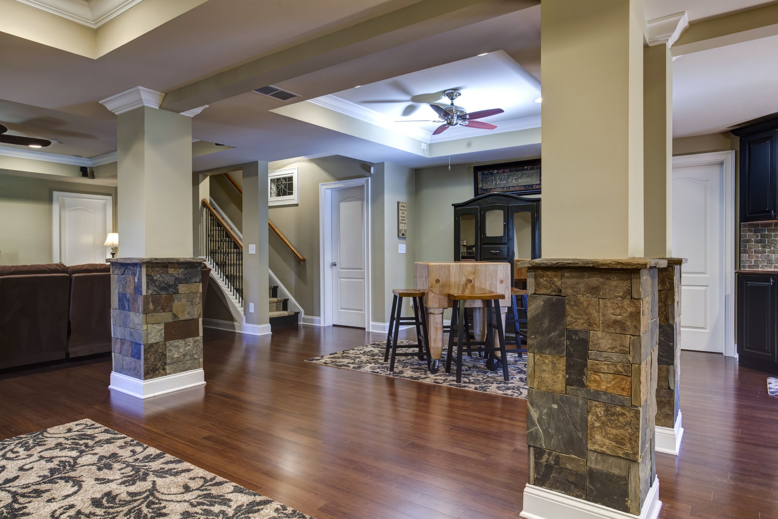 Basement With Hardwood Floors, Stone Columns, Soffits In Ceiling, Opening