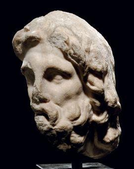 A ROMAN MARBLE FRAGMENTARY HEAD OF ZEUS CIRCA 1ST CENTURY A.D.