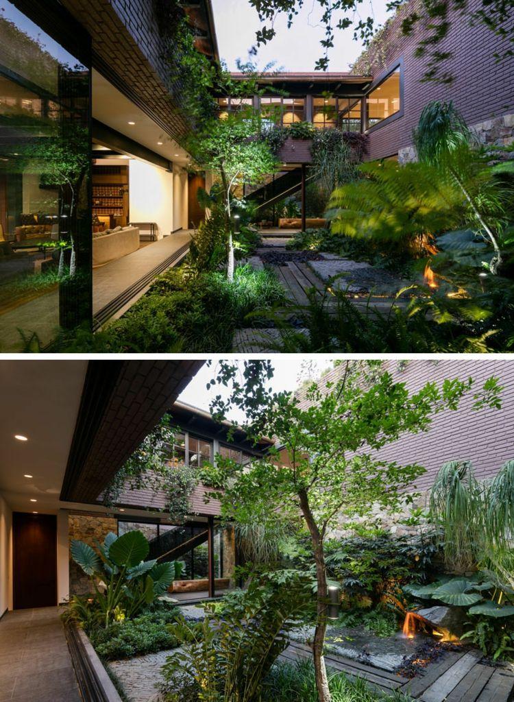 Treppe mit Glasgeländer im modernen Haus, das mit der Natur verschmilzt