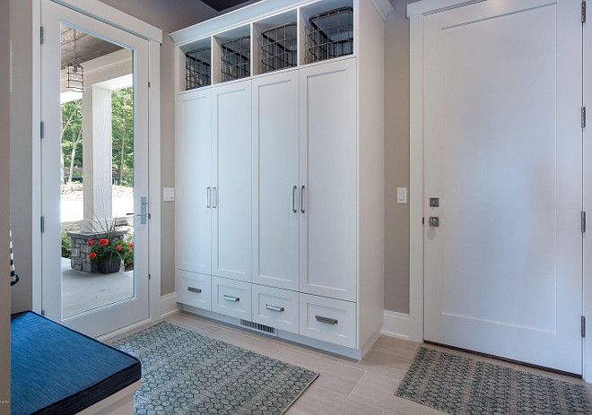 Garage Door Opens To A Mudroom With Tile Floors Closed Cubbies Doors And Small Built In Bench