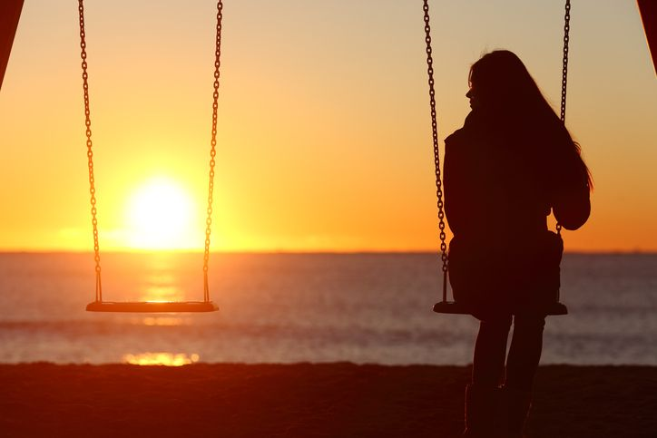 A young woman swings alone, looking at the empty swing beside her.