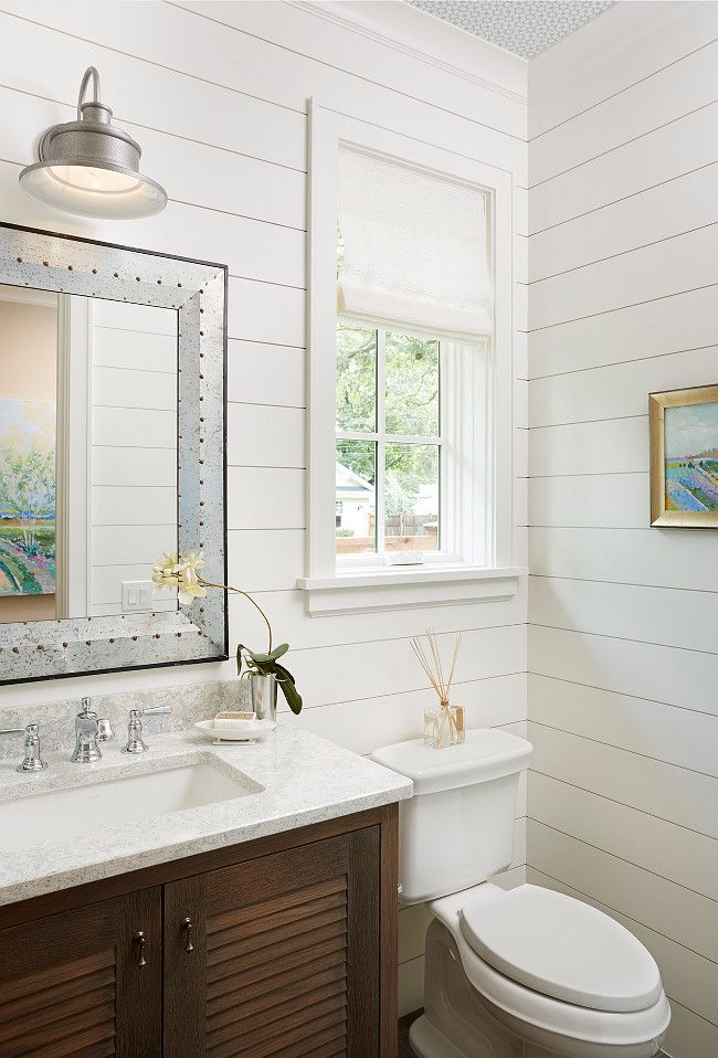 Chic cottage bathroom features shiplap walls lined with a brown louvered  washstand topped with white and gray marble under a beveled rivet mirror. White Shiplap painted in White Dove OC 17 by Benjamin Moore