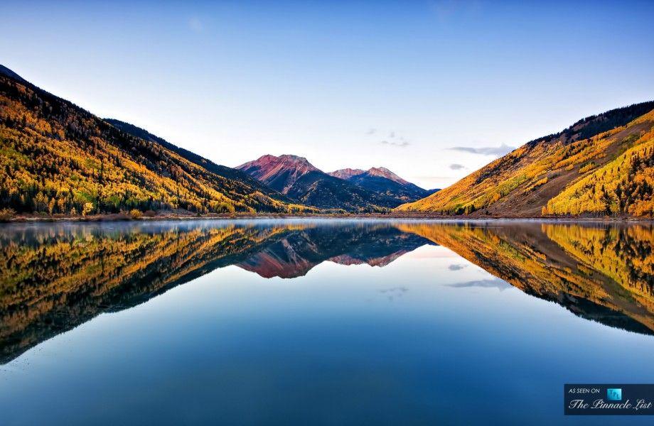 Prístino lago cristalino refleja los colores del otoño en Colorado San Juan Forestal Nacional