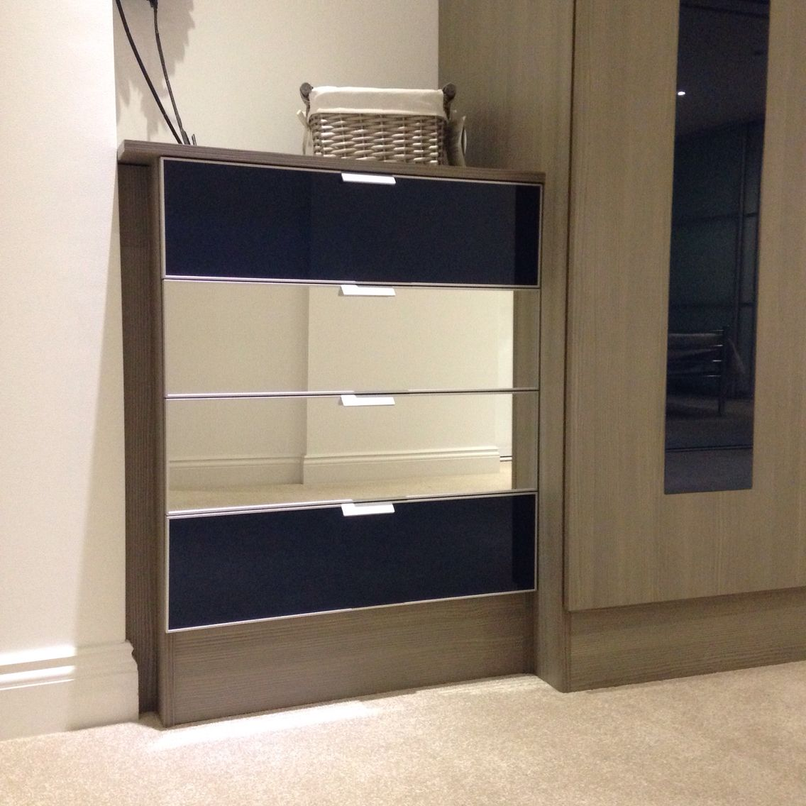 Loft bedroom with no door Petrol blue glass and mirrored drawer fronts  Recent wardrobe