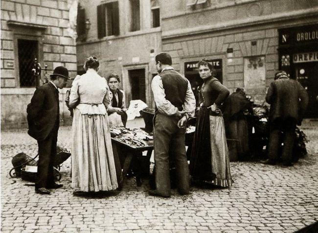 Anonimo, Esterno di rivendita di vini, banco di fotografie e venditore ambulante di castagne arrosto, Roma 1890 ca., gelatina al bromuro d'argento 170x233