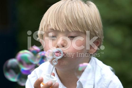 Boy with Down Syndrome blows bubbles royalty-free stock photo