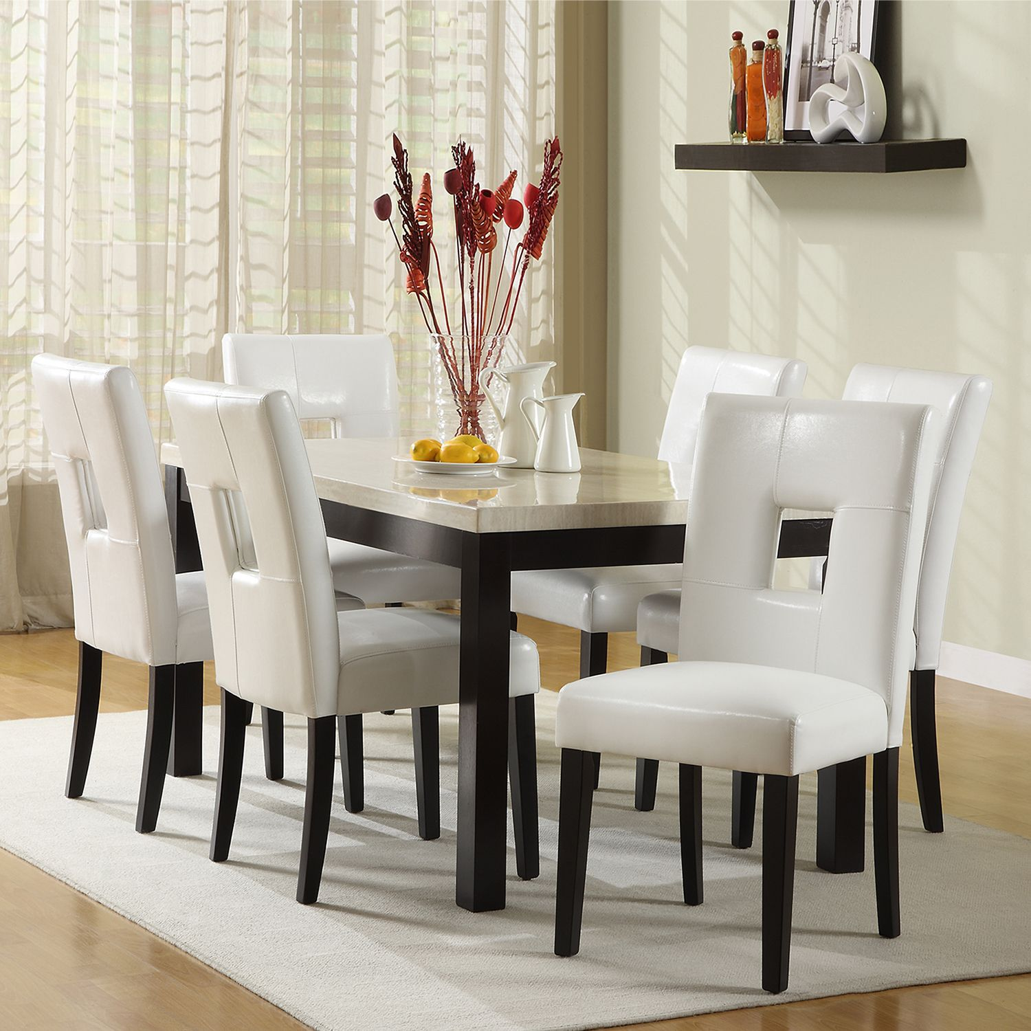This beautiful white 7 piece dining set would make a stylish addition to your dining room. The comfortable white faux leather chairs feature a contemporary cut out back detailing that would make this elegant set ideal for entertaining.