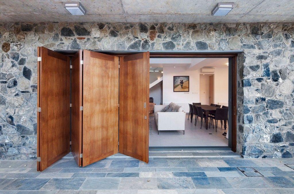 Iroko Wood Bifold Doors And Stone Wall Exterior Also Stone