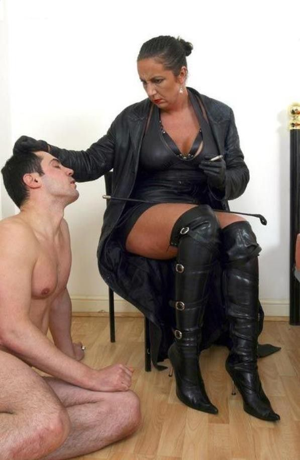 Excellent mature dominatrix in leather smoking casually