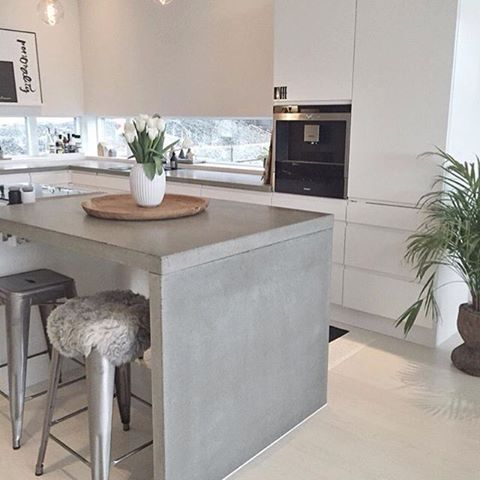 Concrete kitchen island with silver toned stools in a modern minimalist kitchen. Designed by Jke Design Bergen in Norway.