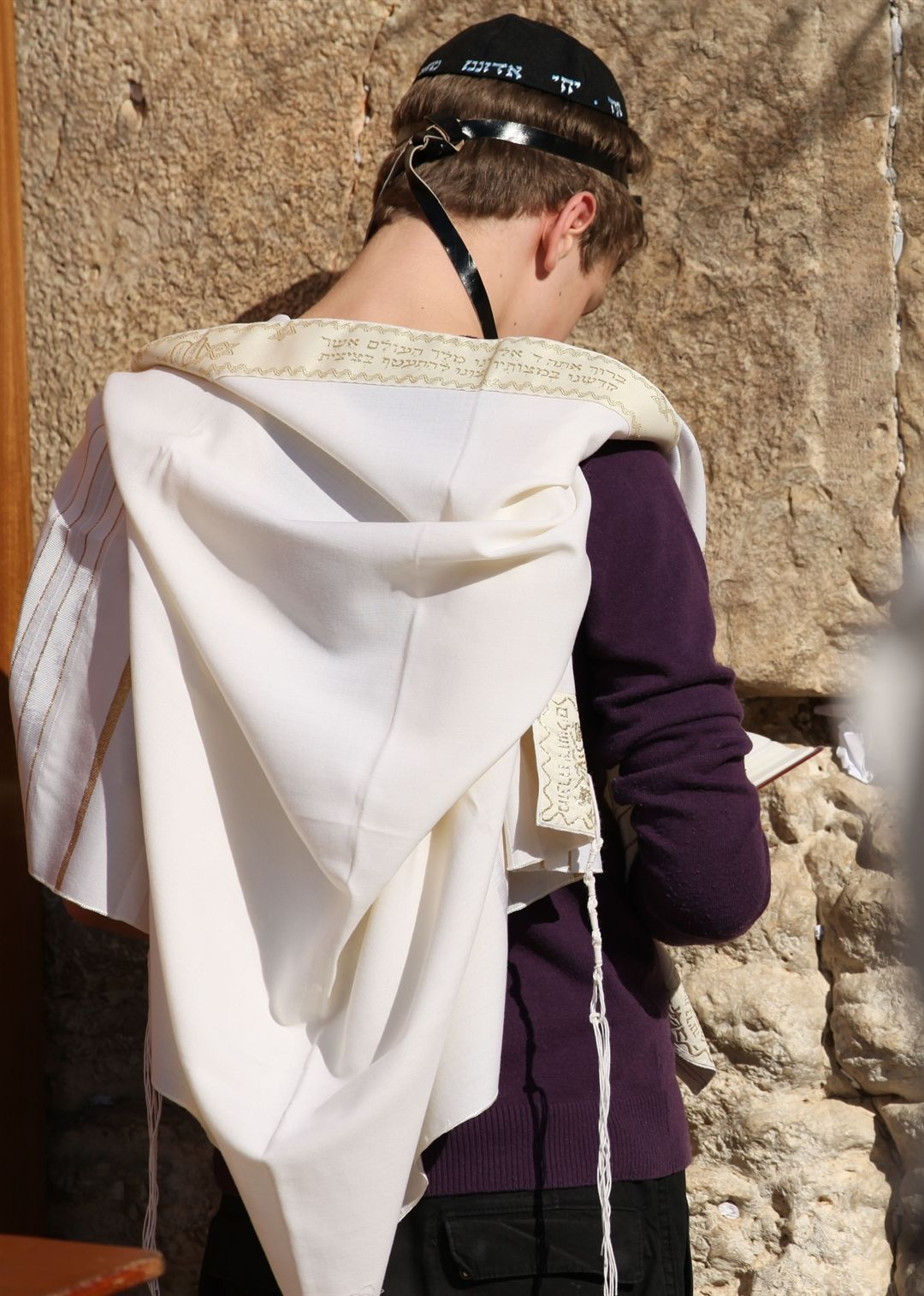 A Jewish teen wearing a tallit (prayer shawl), tefillin ...