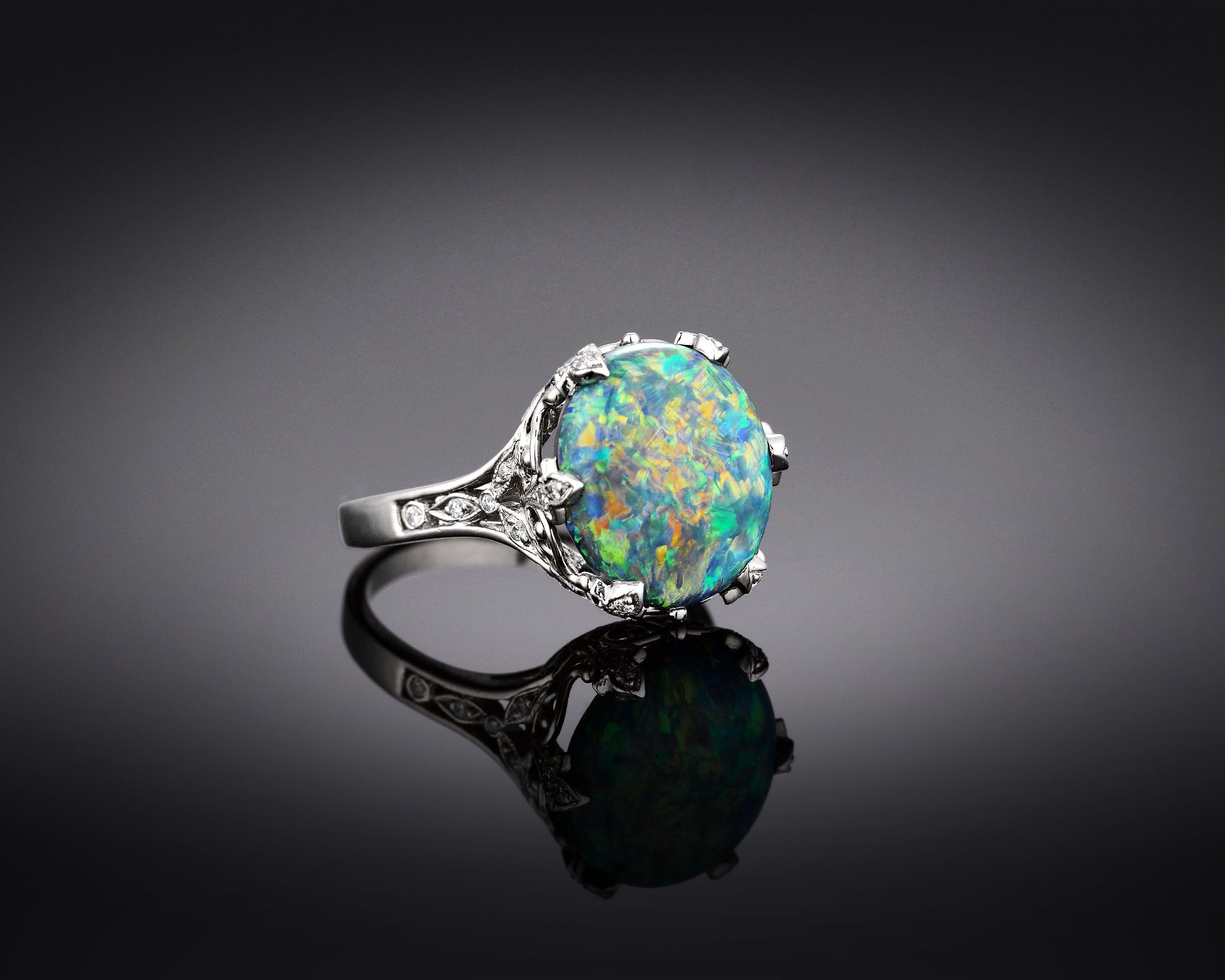 Estate Jewelry, Tiffany & Co., Black Opal Ring ~ M.S. Rau Antiques. A majestic 5.54-carat black opal glistens with a veritable rainbow of color in this Tiffany & Co. ring. This highly desirable gem is set in a fine foliate platinum mounting amongst .25 carats of diamond accents. $34,500