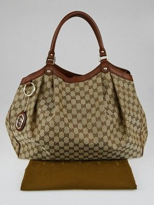 This chic and sophisticated Gucci Beige/Brown GG Canvas Large Sukey Tote Bag is one you won't want to miss out on. With its sleek design and spacious interior, this bag can comfortably hold all your daily essentials. Tote on your arm or over the shoulder with comfortable rolled leather handles. The logo hardware and pleated details are truly a statement of timeless elegance. Retail price is $995.