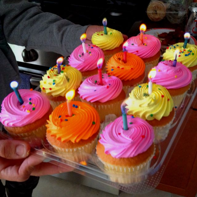 Birthday cupcakes with rainbow colored flame candles.