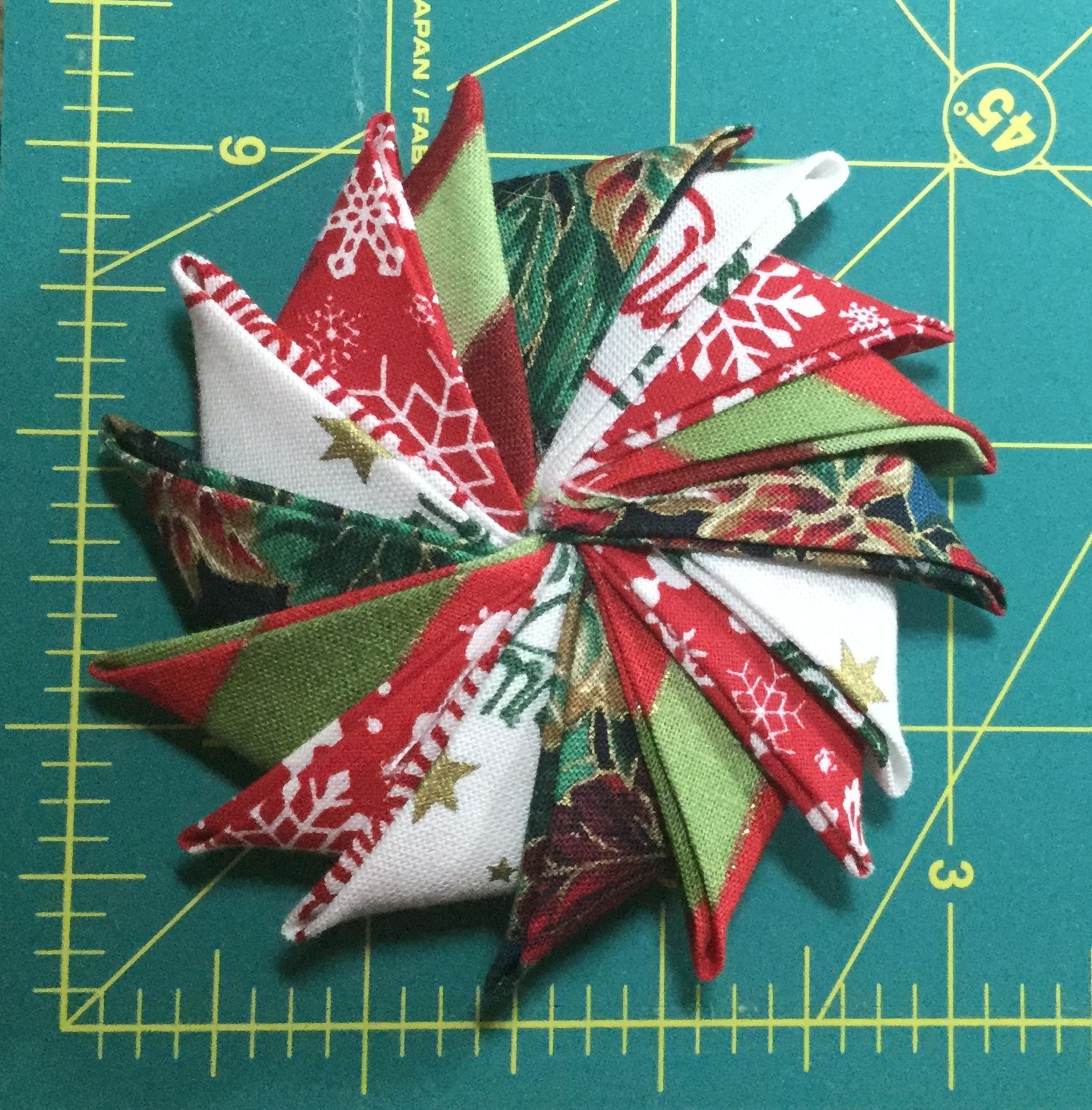 """OK.  I made one, using a 2"""" circle and 2.5"""" squares.  I now need to add the hanging ribbon and center piece.  But I got the measurements figured out from the centimeters used on the original pin.  To make it larger or smaller, the squares need to be 1/2"""" larger than the circle."""