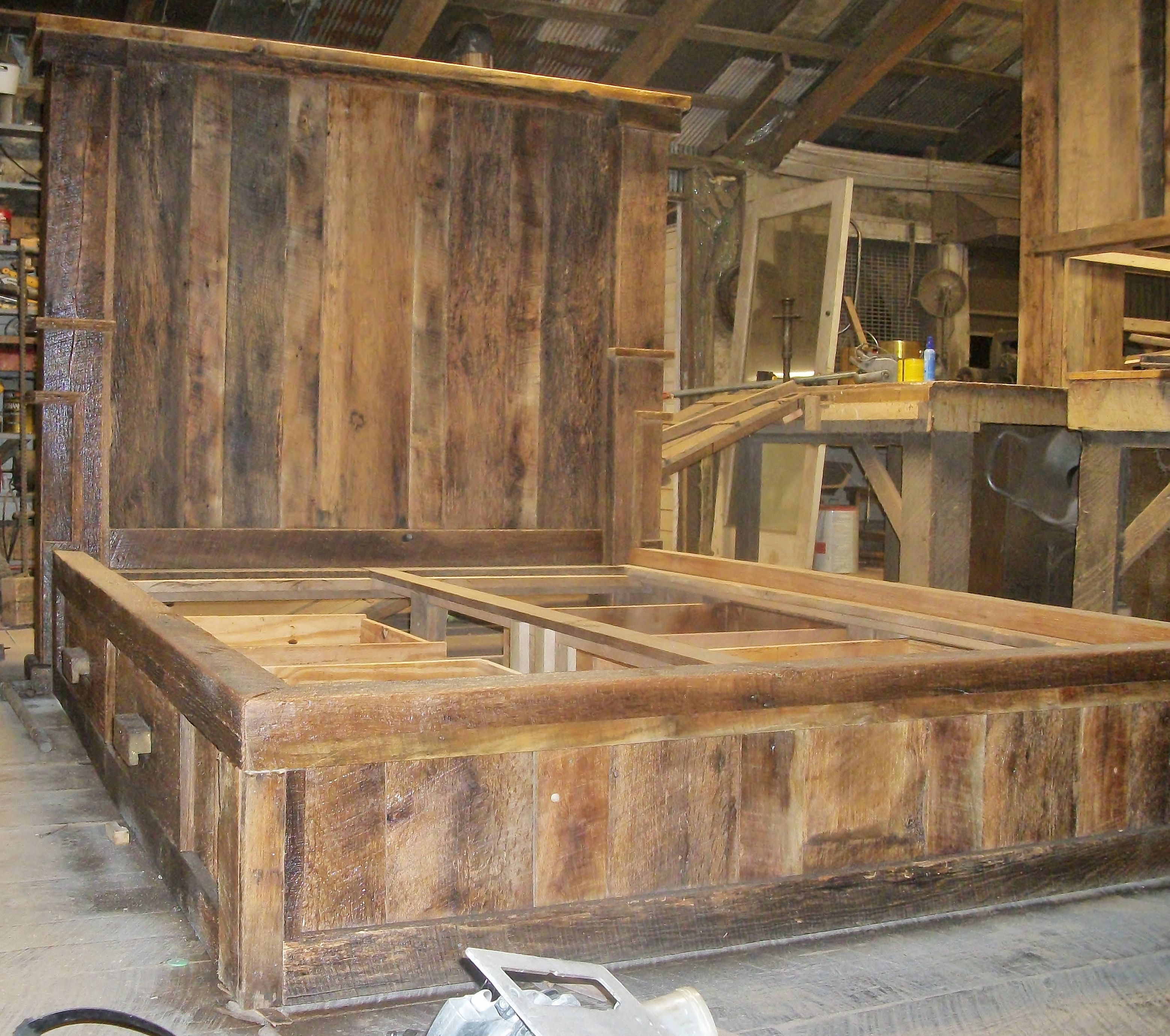 A barn wood platform bed with two drawers on each side for