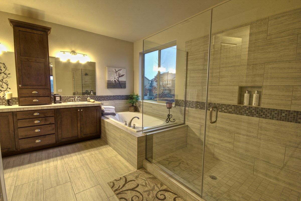 Frameless shower door with garden tub and brown bathroom cabinets ...