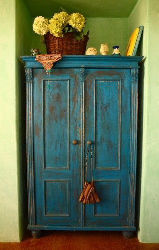Blue armoire against green walls