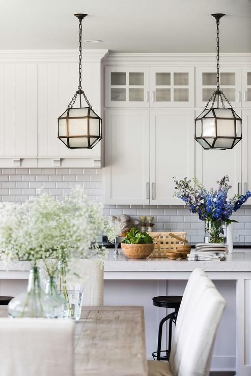 Suzanne Kasler Morris Lanterns Hang Over A White Center Island Topped With Quartz Countertop In Front Of Off Shaker Cabinets And Beveled