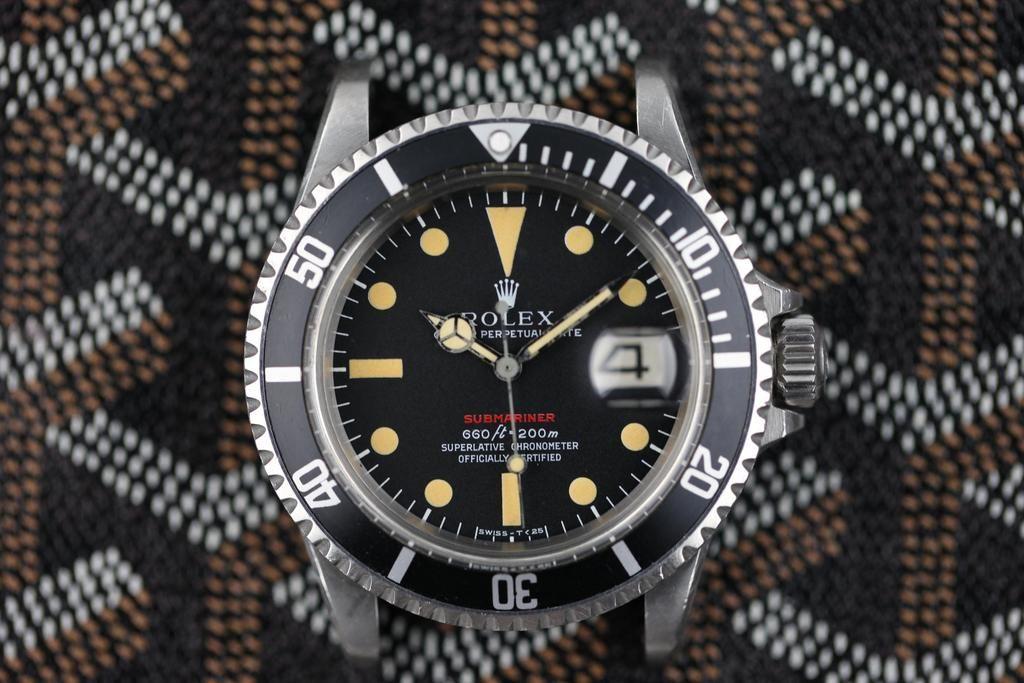 a vintage Rolex Submariner over Goyard leather