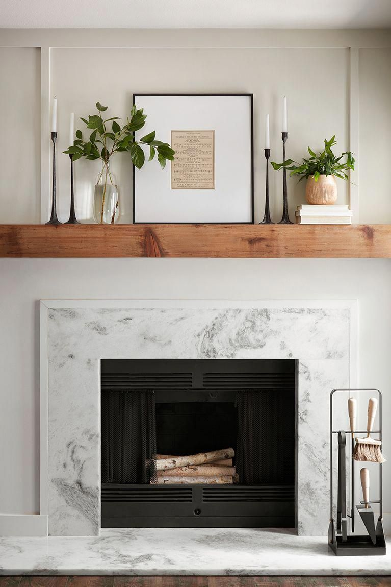 For a timeless mantel setup, we framed a page of sheet music and flanked it with some simple greenery and candlesticks. The marble fireplace surround gives the room a modern detail and a little extra texture. #livingroomdesign
