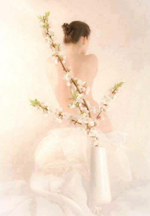 Back view of woman wrapped in white & white flowers  in vase