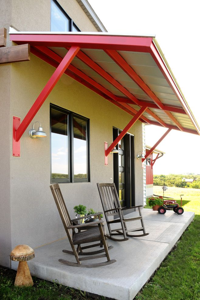Urban Style Front Porch Idea Steel Awning Supported By Red Bars Two Wood Rocking Chairs Concrete