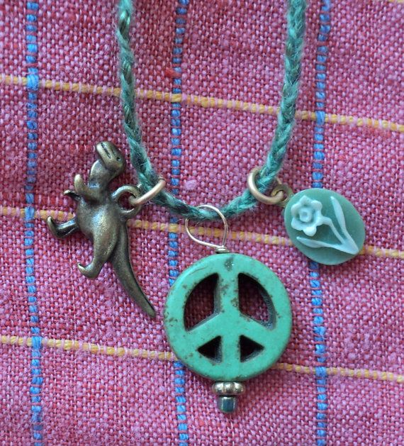 The peace sign dates to 1958, when British artist and activist Gerard Holtom designed the now- familiar symbol for use at a rally calling for nuclear disarmament.    Cameo reminds us of Napoleon, who loved cameos so much he founded a school in Paris to train cameo artisans.    Tiny dinosaur just looks cool.    Hand braided cord is 3 shades of green: 1 is silk, other 2 are recycled cashmere.