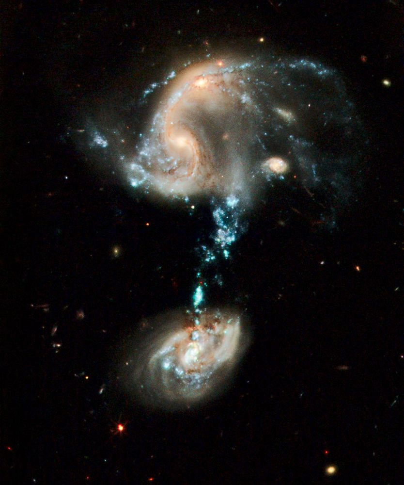 "Arp 194 - This is a merging of three galaxies, all of which have distorted shapes. Arp 194 is about 600 million light-years away in the constellation Cepheus. The blue ""fountain"" is the most striking feature of this galaxy troupe and it contains complexes of super star clusters that may have as many as dozens of individual young star clusters in them"