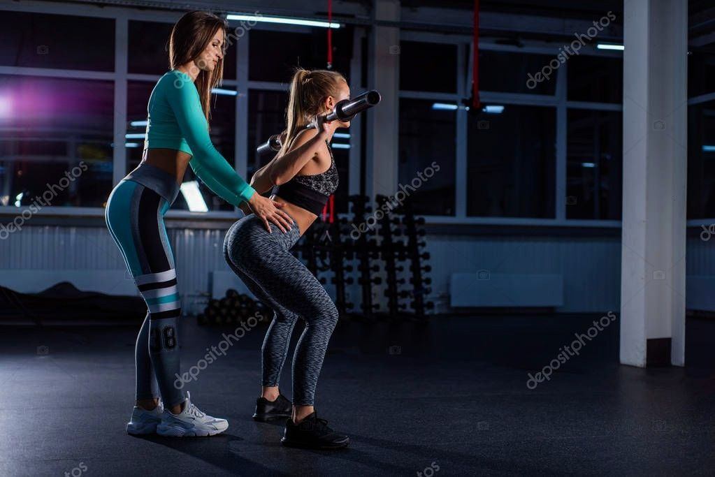 athletic girl doing barbell squats in the gym under the supervision of a t ,Young athletic girl doi