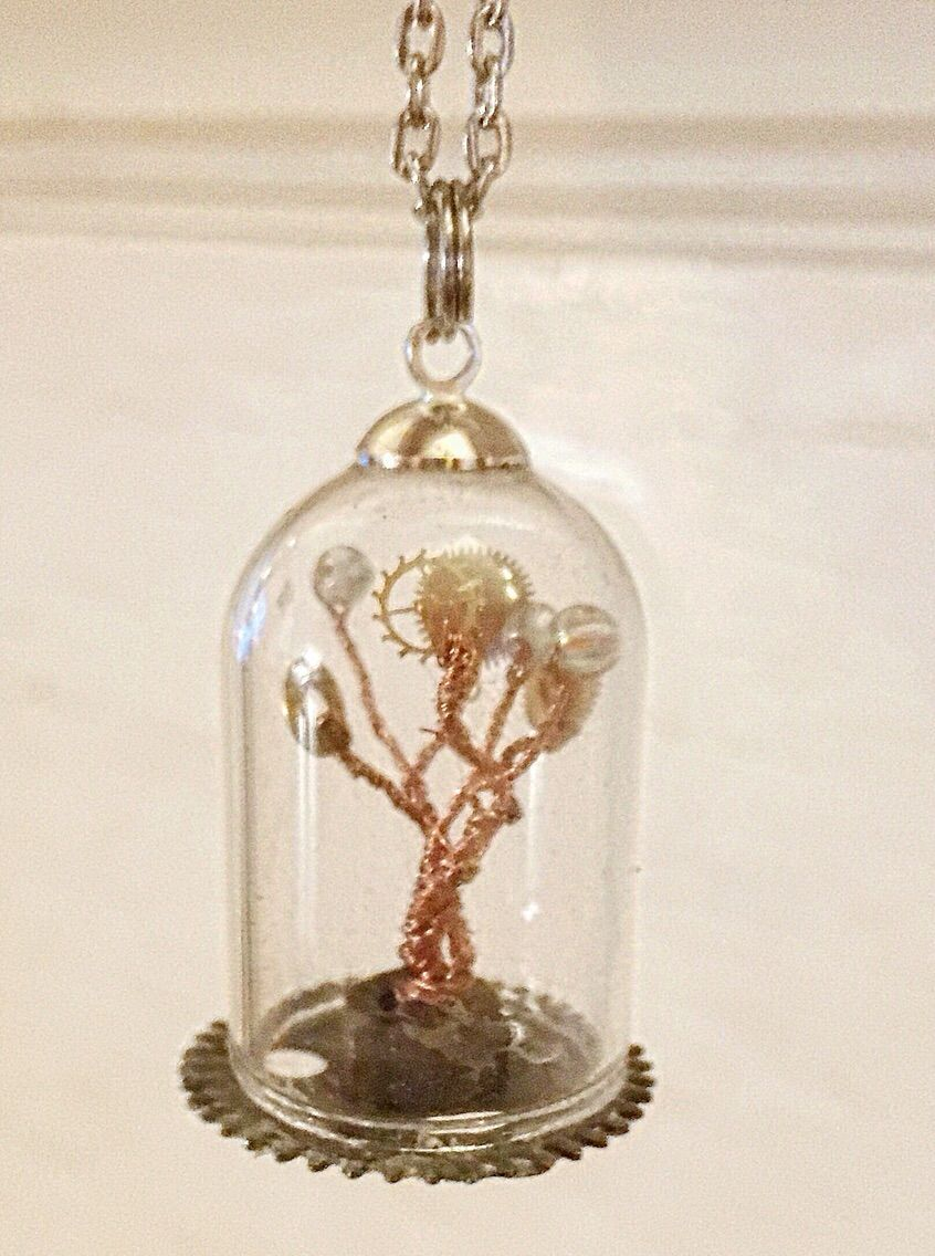 Steampunk Clockwork Tree Glass Dome Pendant Necklace - Unique Handmade upcycled clockwork tree pendant made with upcycled wire and adorned with vintage watch gears and upcycled beads. Measures approximately 1-1/4 inch tall and 3/4 inch diameter, and comes with a silver tone 21 inch chain with lobster clasp.  All of our trees are handmade from upcycled materials.  The wire is recycled from defunct power and audio cords, which we strip down and turn into tiny trees. All watch parts are vintage…