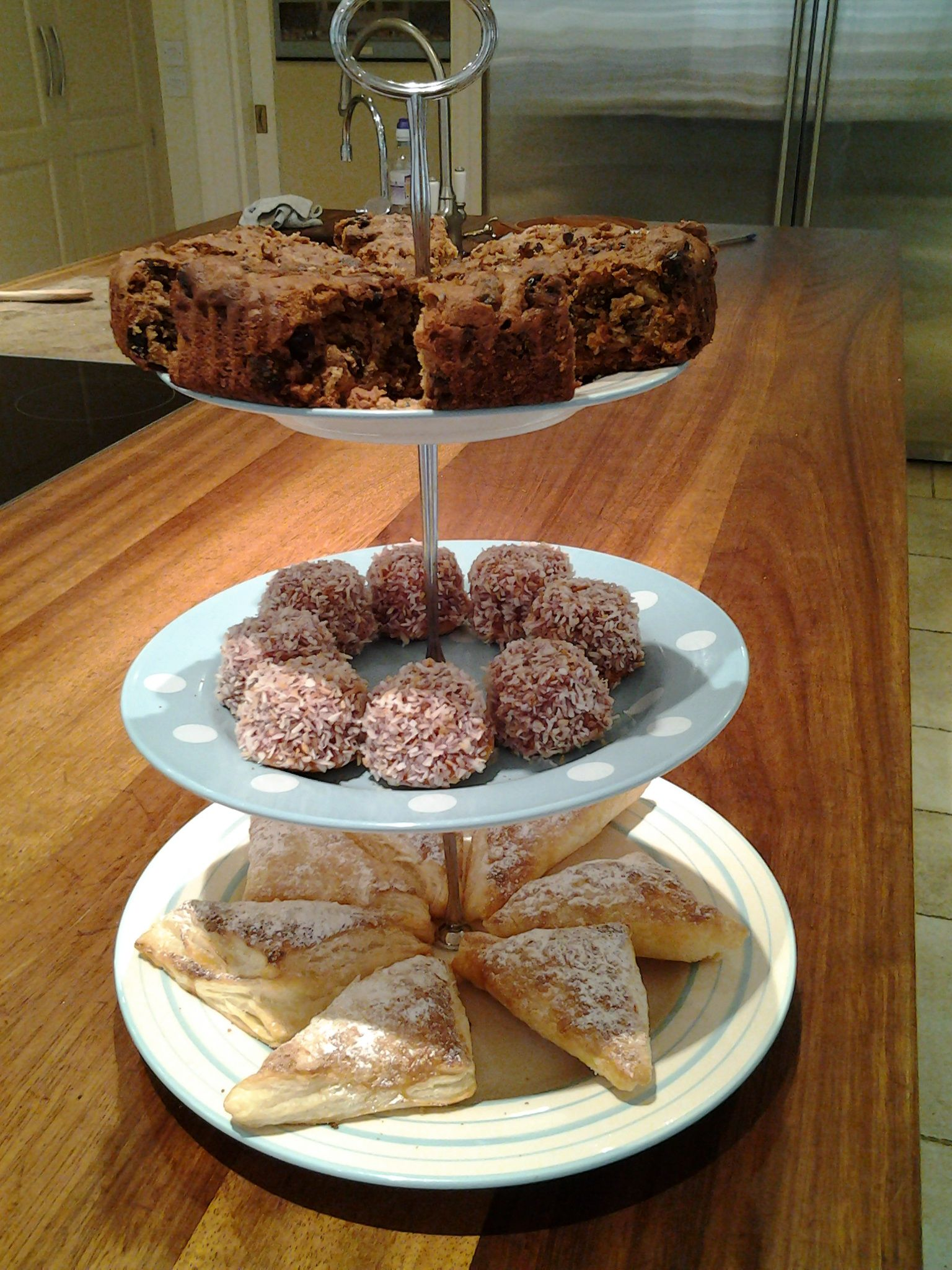 Afternoon tea cake stand, three different cakes every day, here we have a rich sherry fruit cake, coconut maderlains, and lemon puffs.