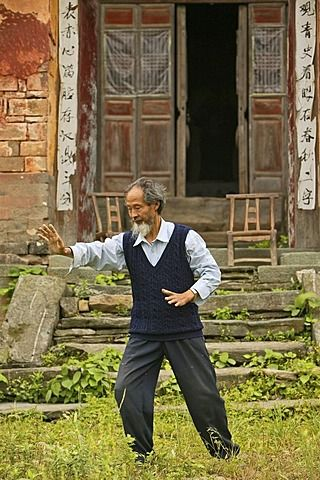 Taichi master demonstrating Taichi in front of his old house at the foot of Mount Wudang - China