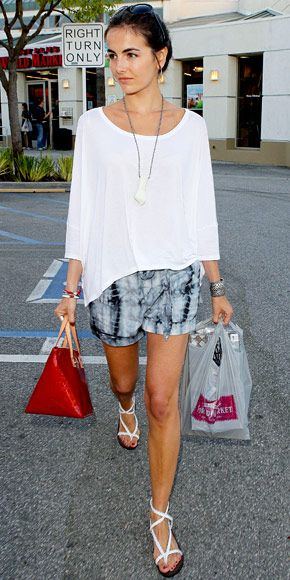 Camilla Belle WHAT SHE WORE Belle hit an L.A. store in tie-dye Habitual shorts paired with a cotton blouse, strappy Joie sandals and a red Louis Vuitton tote. like it