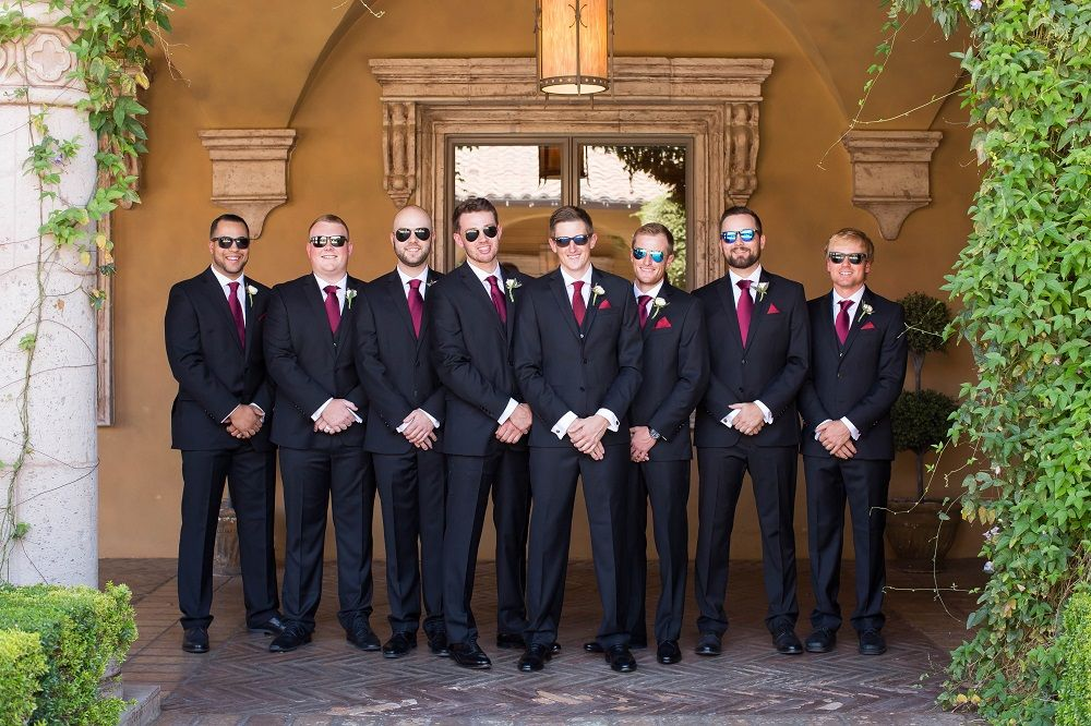 groomsmen posing outside in a courtyard while wearing sunglasses