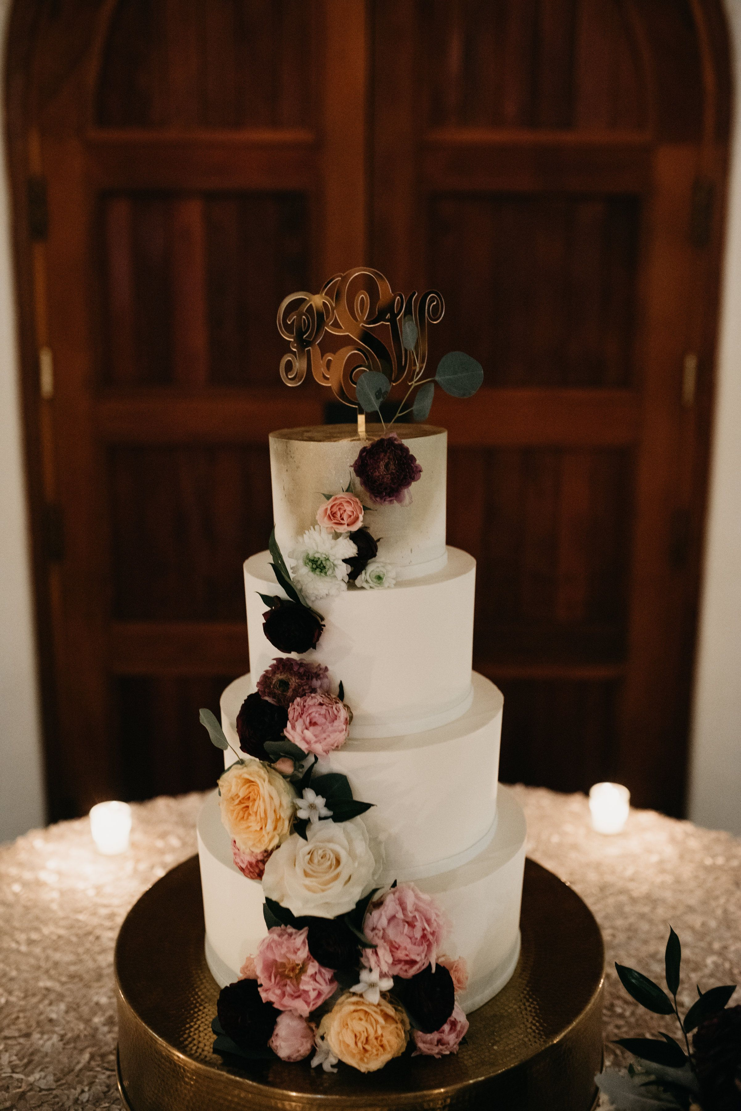 Modern Wedding Cake With Gold Airbrushing And Lush Florals Set On A