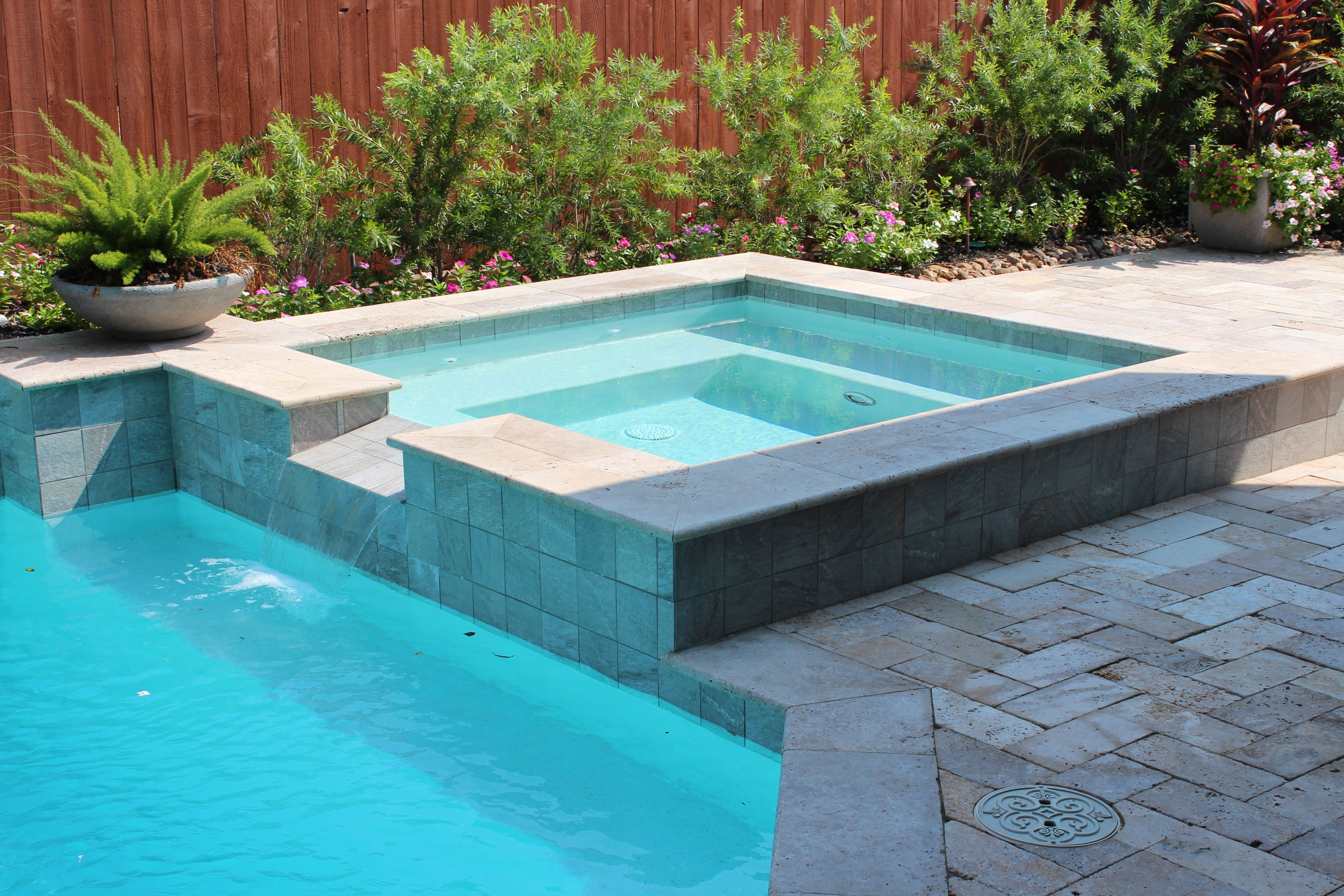 Swimming pool Square spa with tile spillover. Travertine