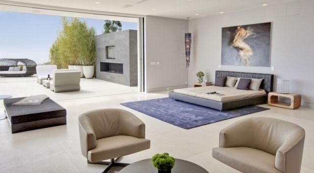 un lit moderne et deux fauteuils blancs dans la chambre à coucher