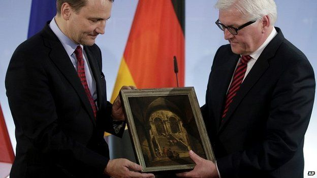 "German Foreign Minister Frank-Walter Steinmeier (R) passes the ""Palace Stairs"" painting to his Polish counterpart Radoslaw Sikorski"