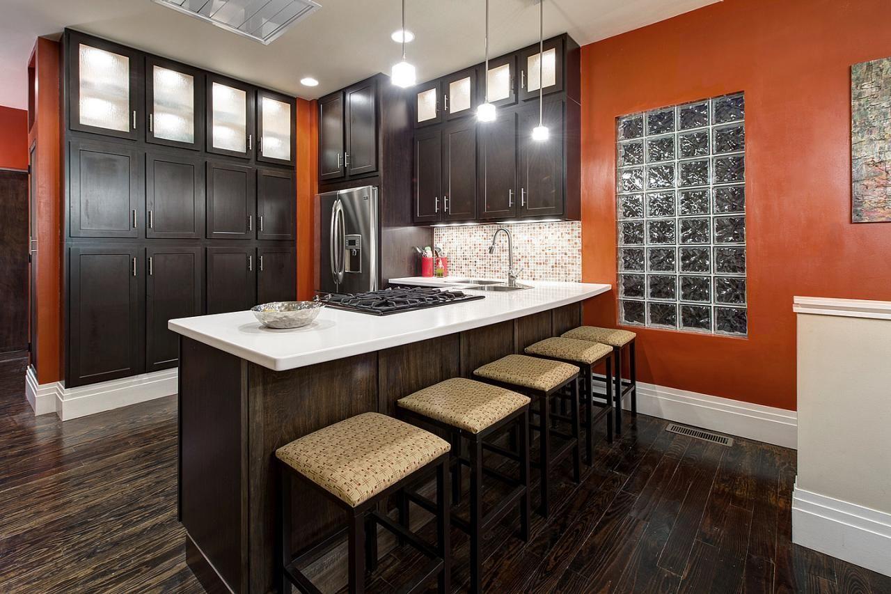 Bold Orange Kitchen Features Dark Wood Cabinetry And Dark Wood Flooring Orange Kitchen Walls Orange Kitchen Kitchen Design