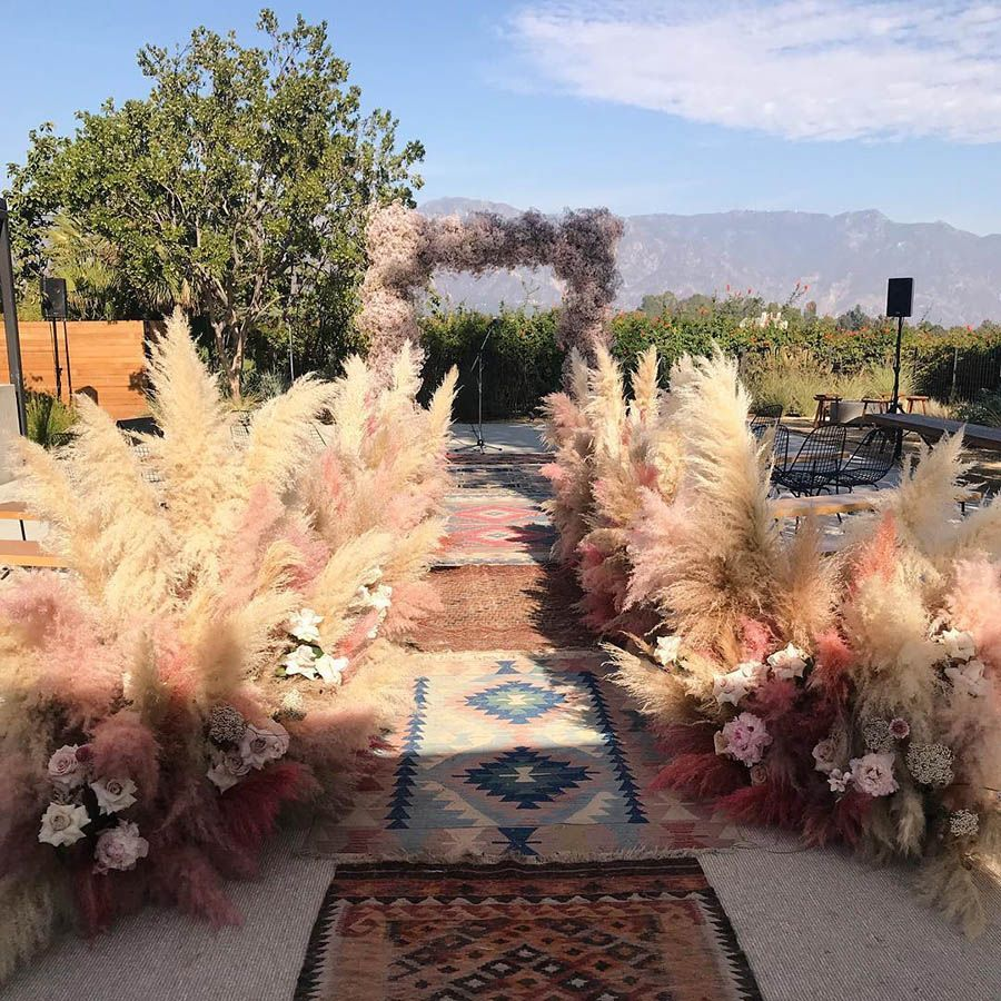 Pampas grass-lined wedding aisle and a rectangular arch covered in dyed-pink baby's breath | Mandy Moore and Taylor Goldsmith's Intimate Boho Wedding in Los Angeles #boho wedding aisle Mandy Moore and Taylor Goldsmith's Intimate Boho Wedding in Los Angeles