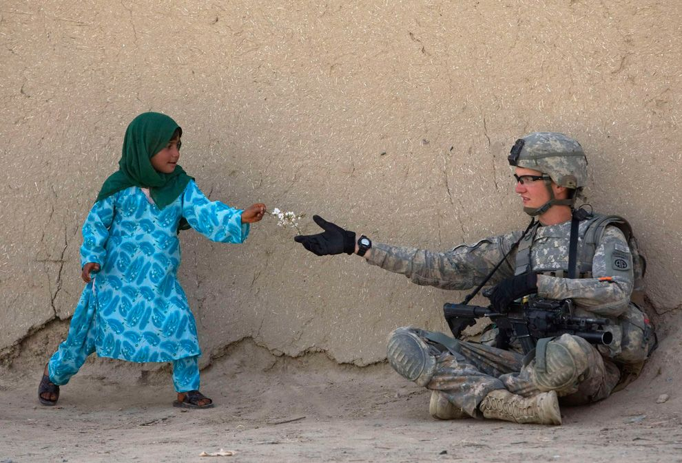 U.S. Army Private First Class Danny Comley of Camdenton Missouri, assigned to Delta Company 4th Brigade combat team,2-508, 82nd parachute infantry Regiment, receives flowers from an Afghan girl during a patrol in the Arghandab valley in Kandahar province, southern Afghanistan February 24, 2010.