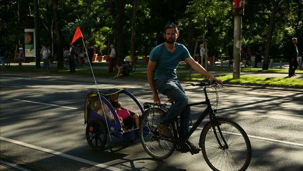 Pais leva filhos na bicicleta cargueira em Viena, Áustria.