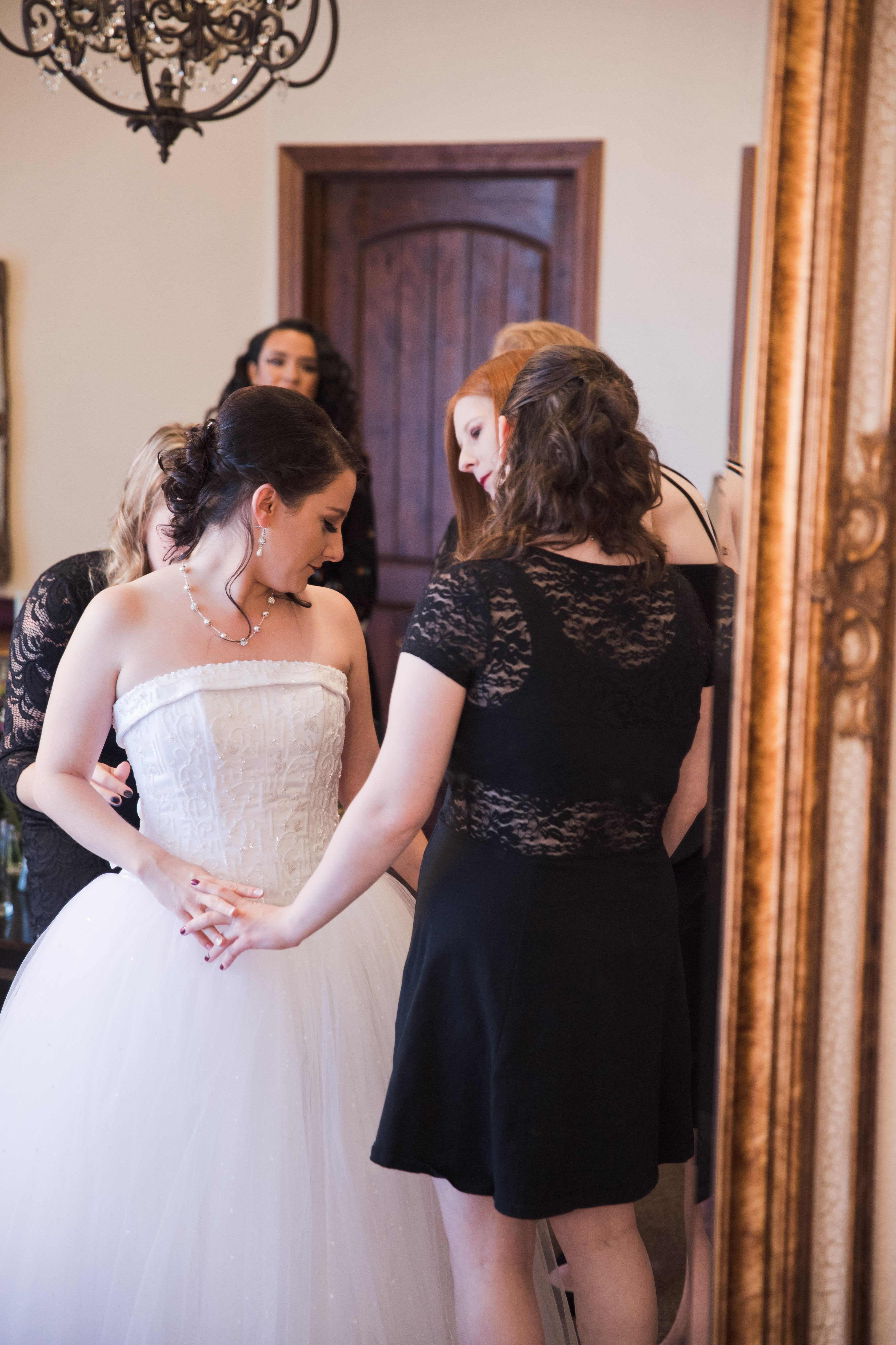 Bridesmaids helping this pretty bride get in her wedding dress ...