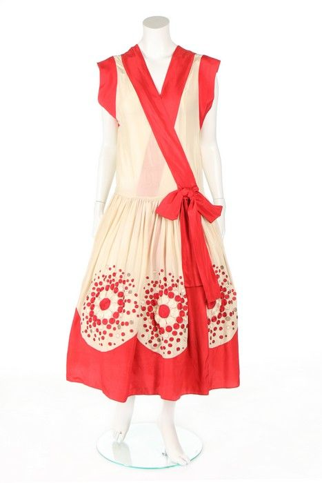 A Jeanne Lanvin couture robe de style, 'La Mascotte', Spanish collection, 1925. un-labelled, of ivory crêpe de chine edged in scarlet, with cross-over front panels, with red silk ties to waist, the skirt embroidered with chain stitched roundels in scarlet and ivory, edged in gold thread, the inner hem with stiffened scalloped band to hold the shape, bust approx. 86-92cm, 34-36in.Zoomed Image